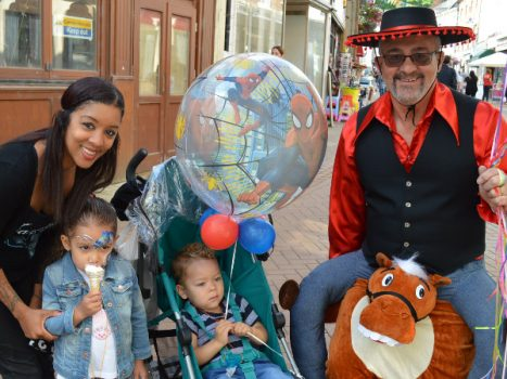Laura Walker with children Ilaria and Kit get a balloon from Ken Gillett of Sweet Celebrations in Church Lane.