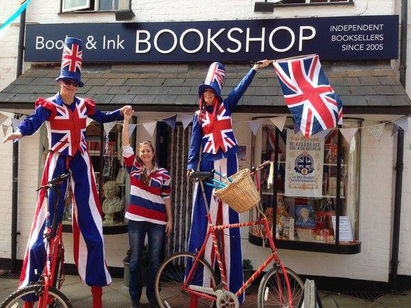 Banbury Old Town Spring Party 2016.  San Barnes outside her Books & Ink Bookshop with the Stilt Walkers